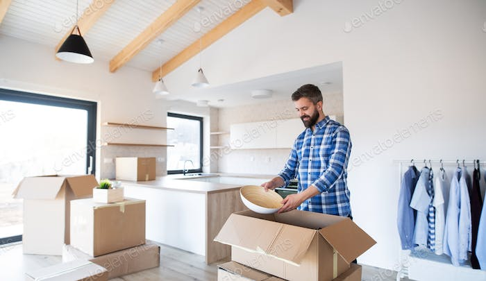 Mature man with boxes moving in new unfurnished house.