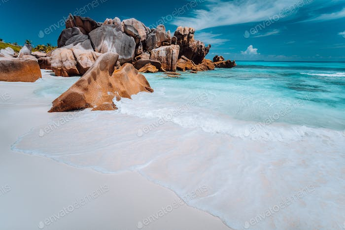 Granite rocks boulders, perfect white sand, turquoise water, blue sky. paradise beach Anse Cocos on