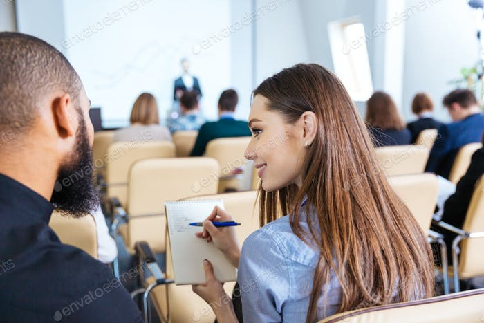 Two young people writing and talking on business meeting