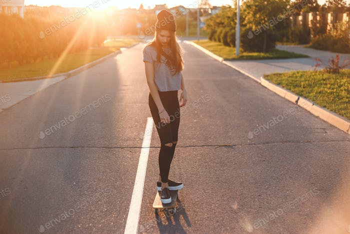 Young woman down the road with a skateboard.