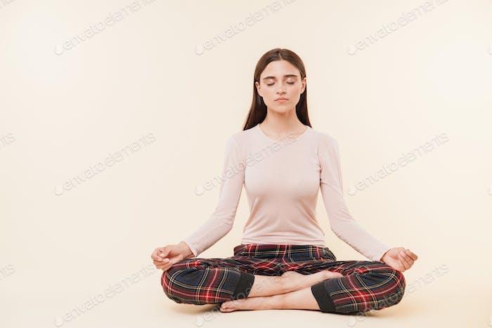 Pretty young brunette girl meditating