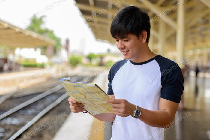 Young handsome Asian tourist man at the railway station