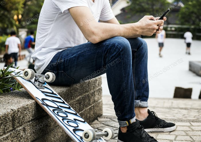 Young adult skateboarder using a smartphone youth culture concep