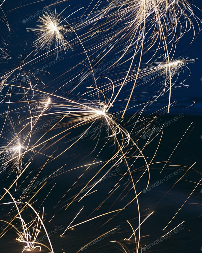 Long exposure of fireworks bursting into light over the beach at Long Beach Peninsula