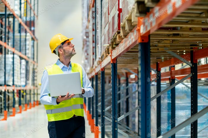 Manager of warehouse check inventory with laptop walking between shelves