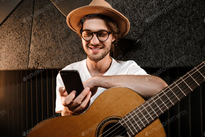 Young attractive man with guitar happily using smartphone in modern sound recording studio