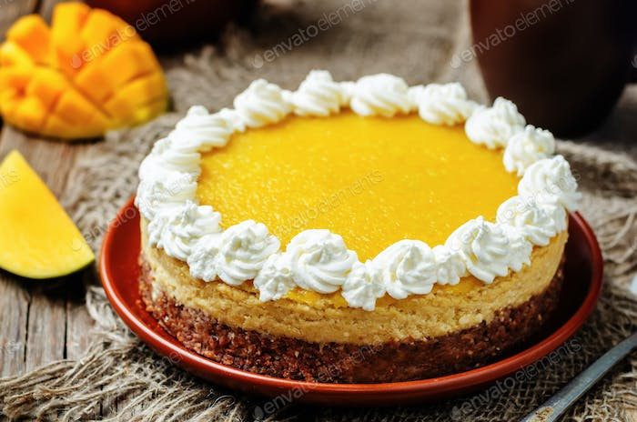mango cheese cake decorated with whipped cream and mango puree