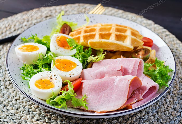 Breakfast with cornmeal waffles, boiled egg, ham and tomato on dark background.
