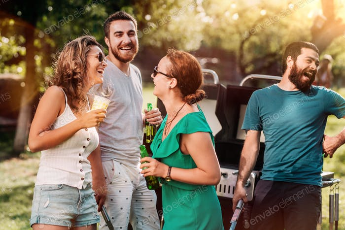 Group of friends having drinks and laughing at barbecue party, summer outdoor backyard concept