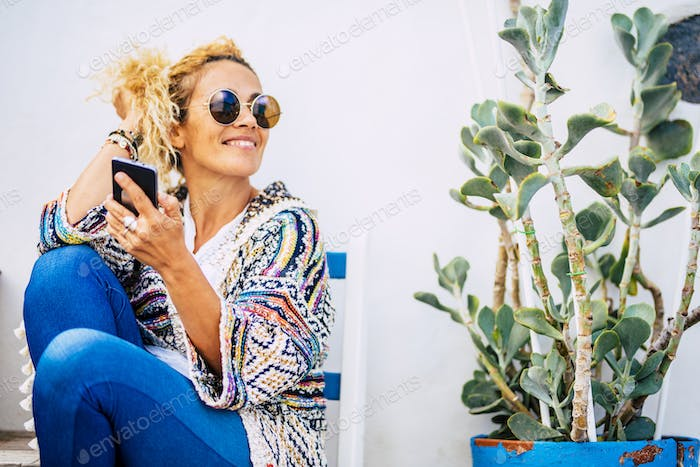 Cheerful beautiful woman portrait use cellular phone outdoor with plant and blue seats outdoor home
