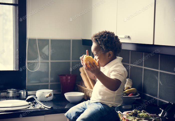 Black kid with orange in the kitchen