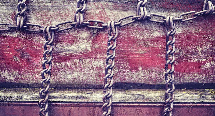 Vintage stylized chains on old wooden wall.