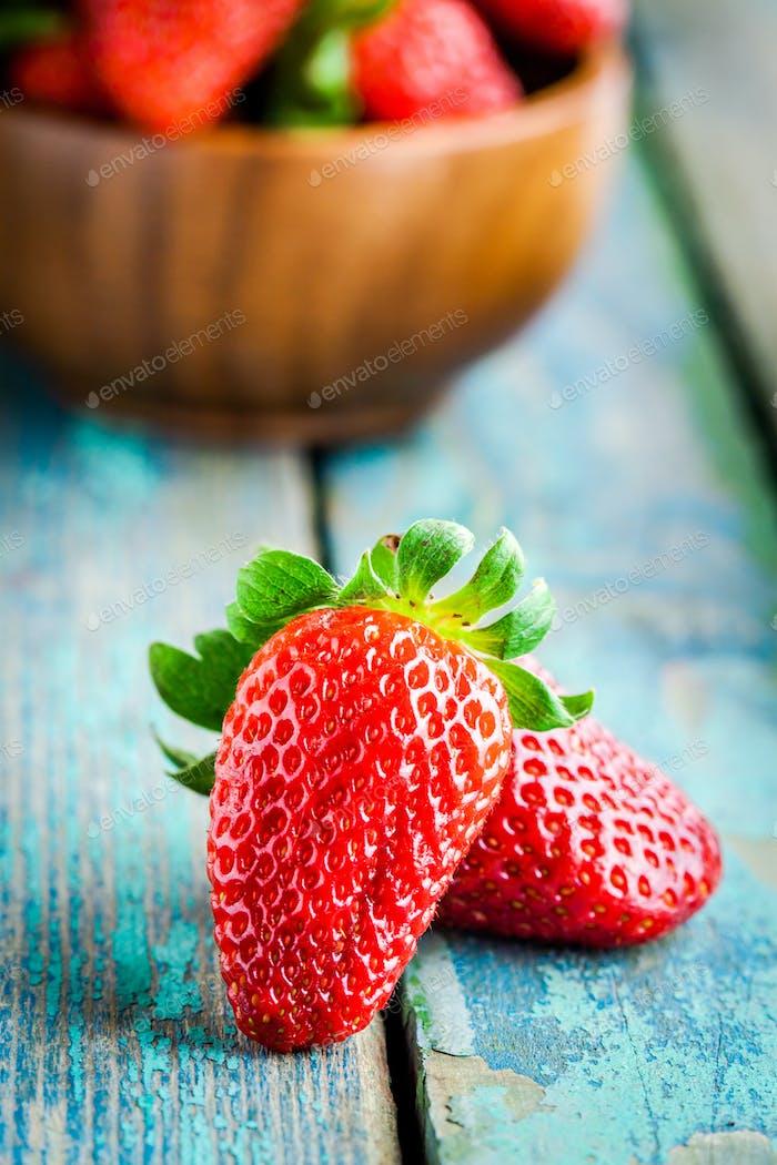 Fresh ripe organic strawberries in a wooden bowl closeup