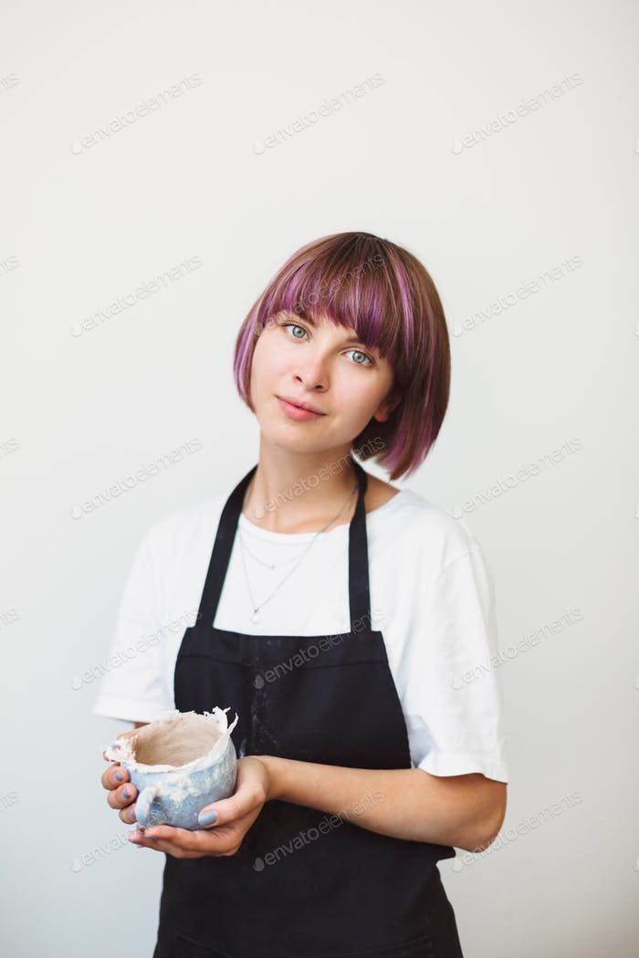Beautiful girl with colorful hair in black apron and white T-shirt holding handmade little bowl