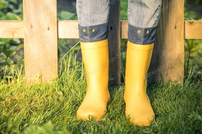 Yellow wellies and jeans in garden,toned image