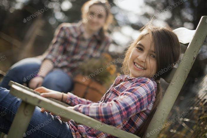 Dos niños sentados al aire libre en un jardín en una granja ecológica.