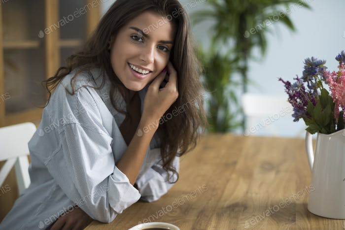 Young woman drinking coffee in the dining room
