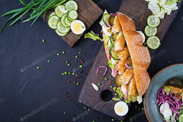 Baguette-Sandwich mit Fisch, Ei, eingelegten Zwiebeln und Salatblättern. Ansicht von oben