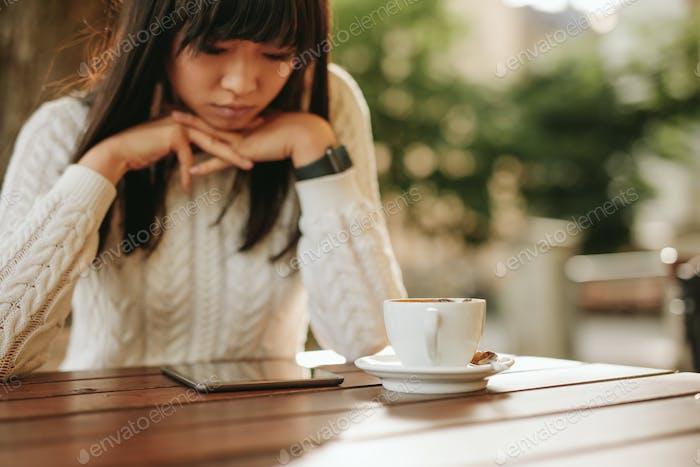 Junge Frau mit digitalem Tablet in einem Café