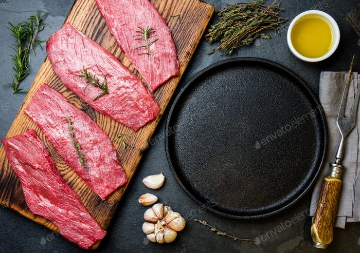 Beef tenderloin in cast iron pan on wooden board, spices, herbs, oil on slate gray background