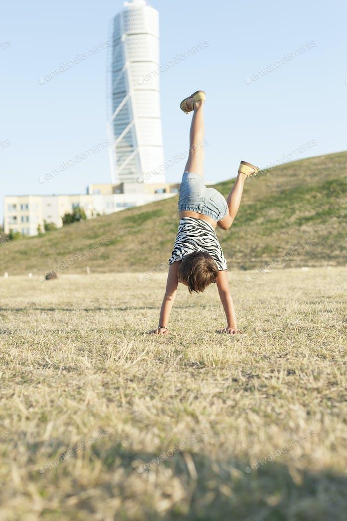 Little girl doing handstand on field in city