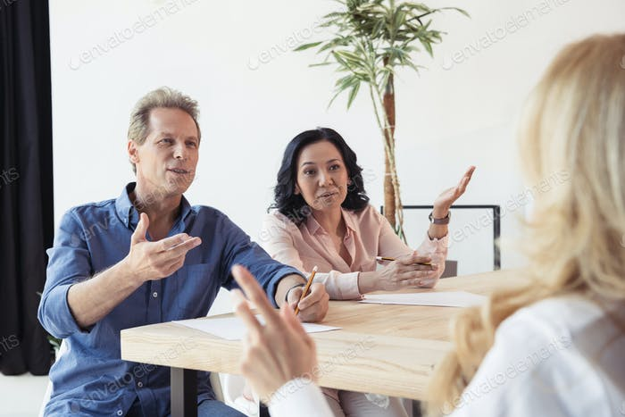 middle aged colleagues disputing at business meeting in office