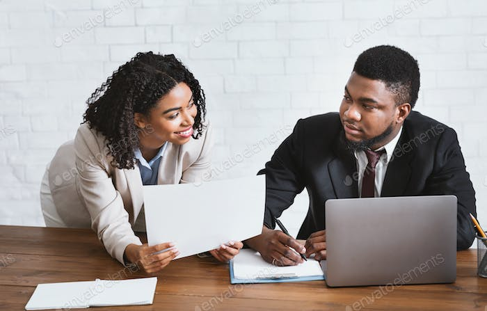 Sexual harassment in office. Black businesswoman flirting with her displeased male secretary at