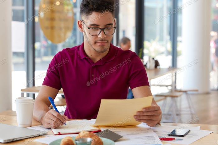 Horizontal shot of serious banker holds paper, writes creative ideas for development of successful b