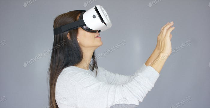 Entzückende Frau arbeitet mit Virtual Reality Brille