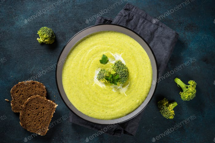 Broccoli cream soup in the bowl on dark table