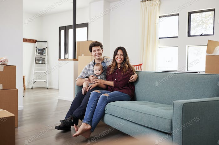 Portrait Of Happy Family With Baby Resting On Sofa Surrounded By Boxes In New Home On Moving Day
