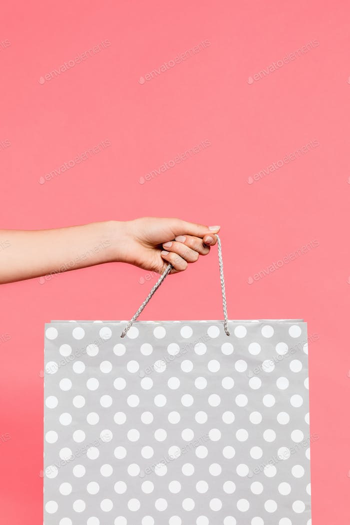 close-up view of hand holding shopping bag isolated on pink