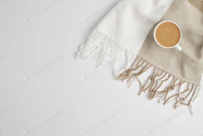 Flat lay of cup of fresh aromatic cappuccino on checkered linen or cotton scarf