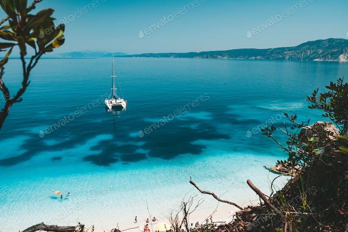 Weiße Katamaranyacht vor Anker auf klarem azurblauen Wasseroberfläche in ruhiger, blauer Lagune. Unerkennbar