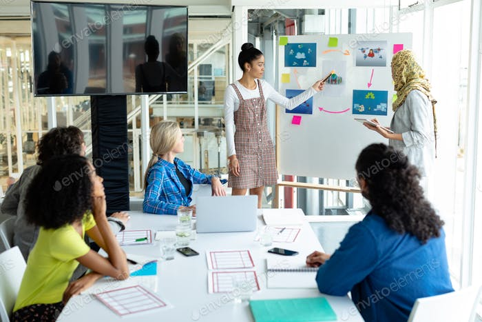 Mixed-race businesswoman giving presentation on flip chart during meeting