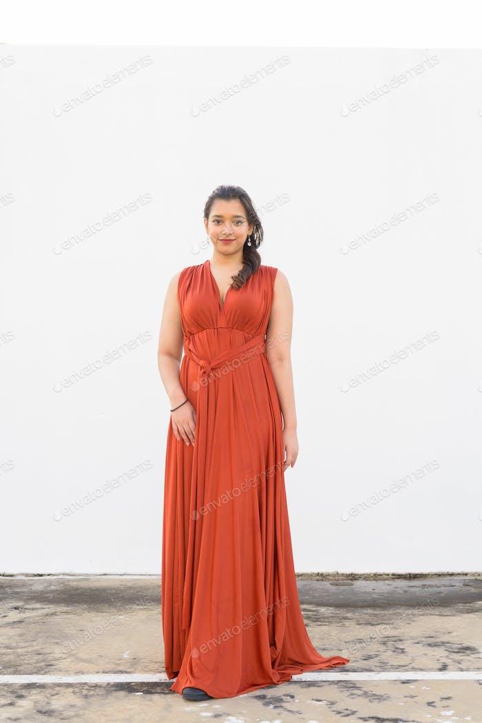 Full body shot of young beautiful Indian woman outdoors