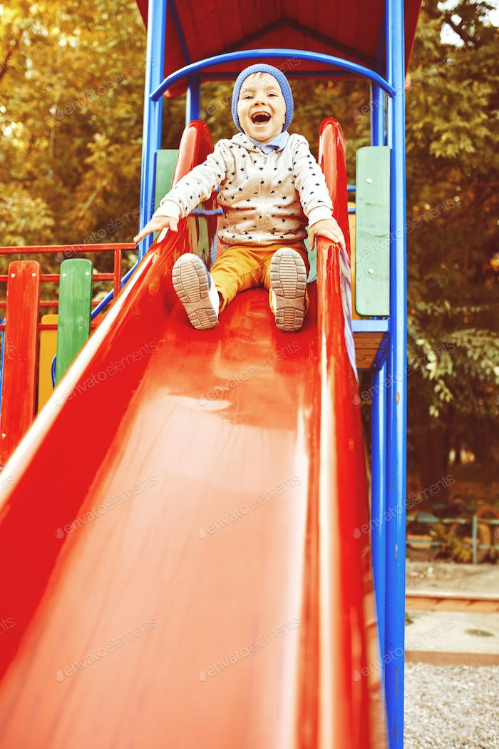 Little boy playing on children's slides