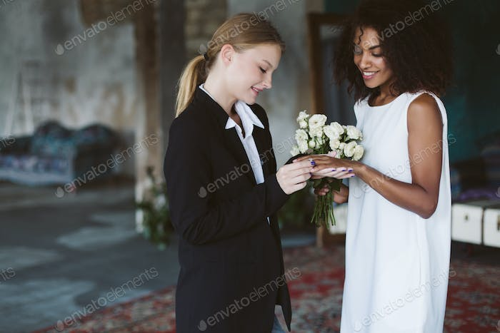 Young pretty woman with blond hair in black suit putting a weddi