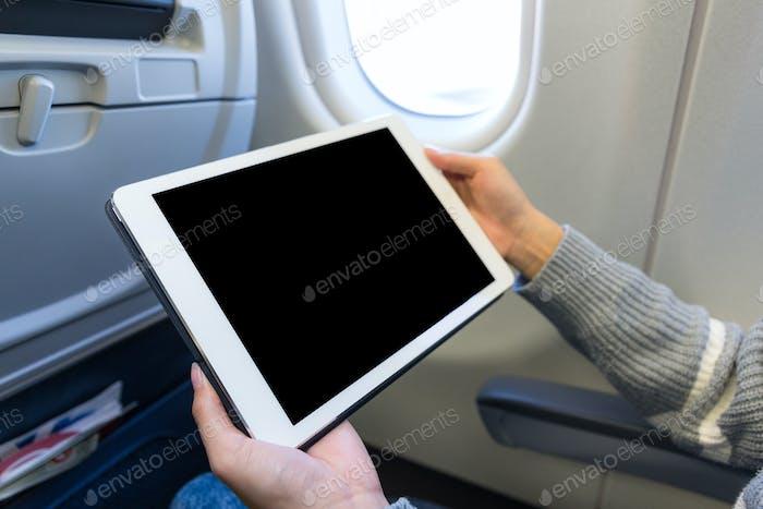 Uso por mujer de la tableta digital en avión