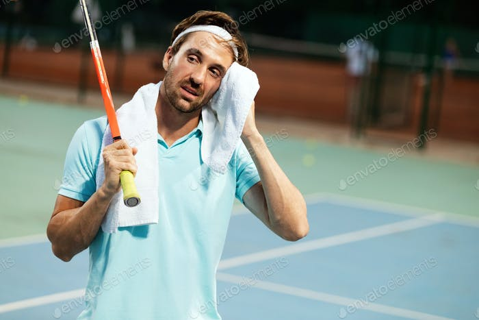 Tired tennis player man on tennis court with racket