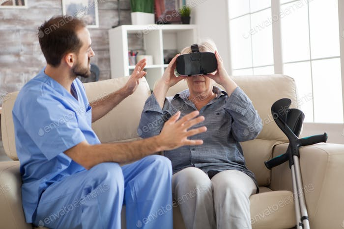Older patient using virtual reality glasses in nursing home