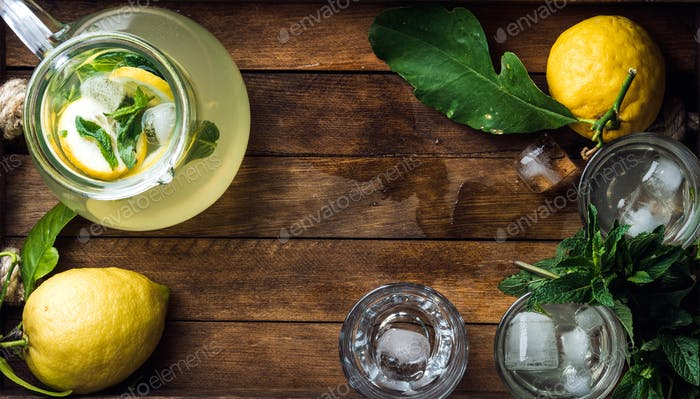 Homemade mint lemonade served with fresh lemons and ice over wooden background, top view, copy space