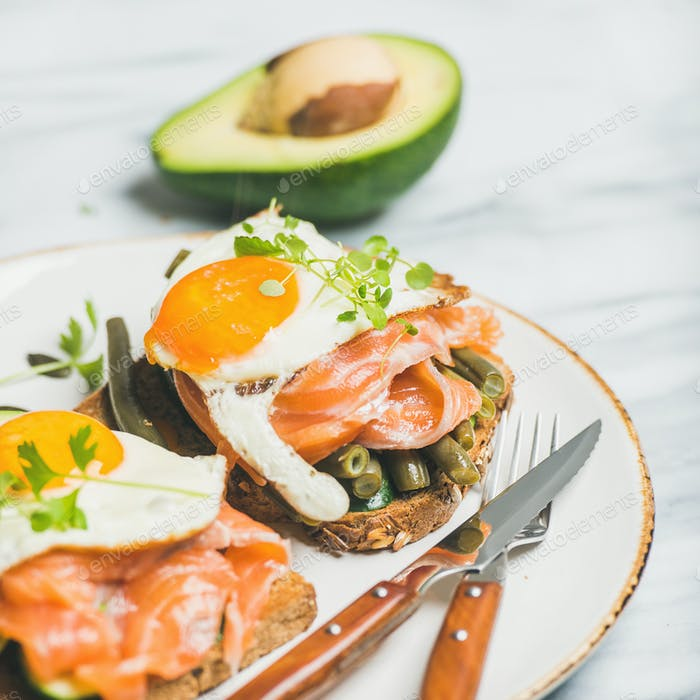 Salmon, avocado, fried egg, beans and sprouts sandwiches, square crop