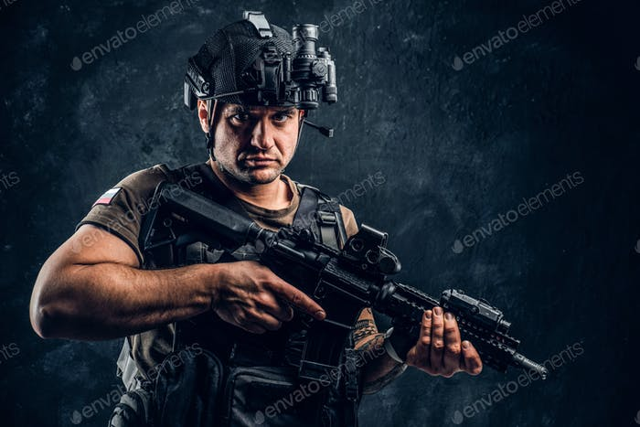 Brutal soldier wearing body armor and helmet with a night vision posing with an assault rifle
