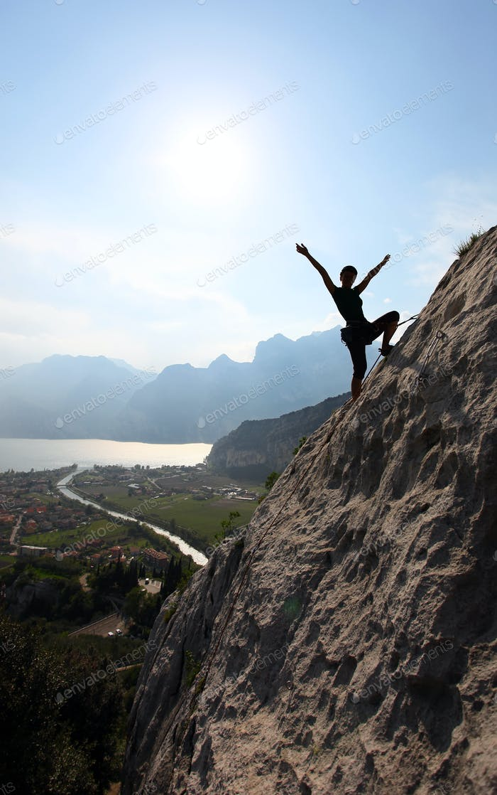 Silhouette of a female rock climber with outstretched arms