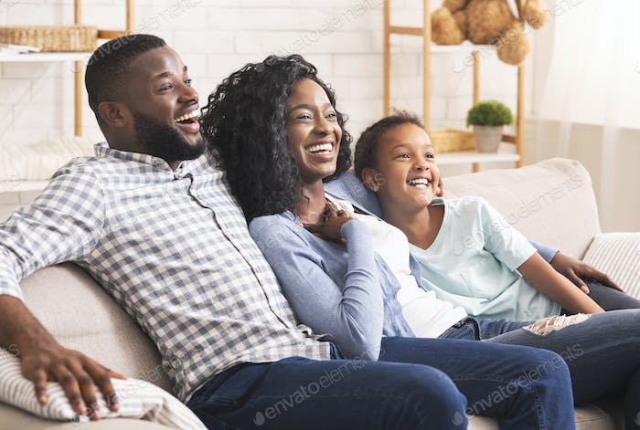 Joyful african american family watching comedy show on tv together