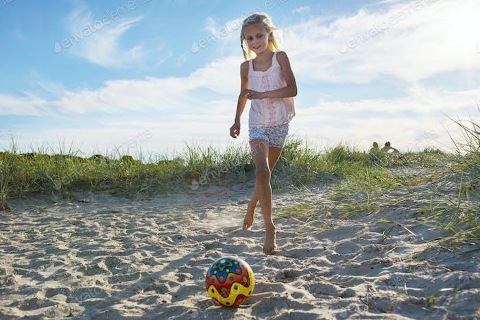 Mädchen (8-9) Kicking Ball am Strand