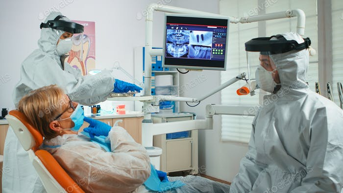 Doctor with face shield pointing on stomatological monitor