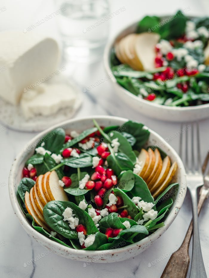 Vegan salad bowl with spinach, pear, pomegranate, cheese