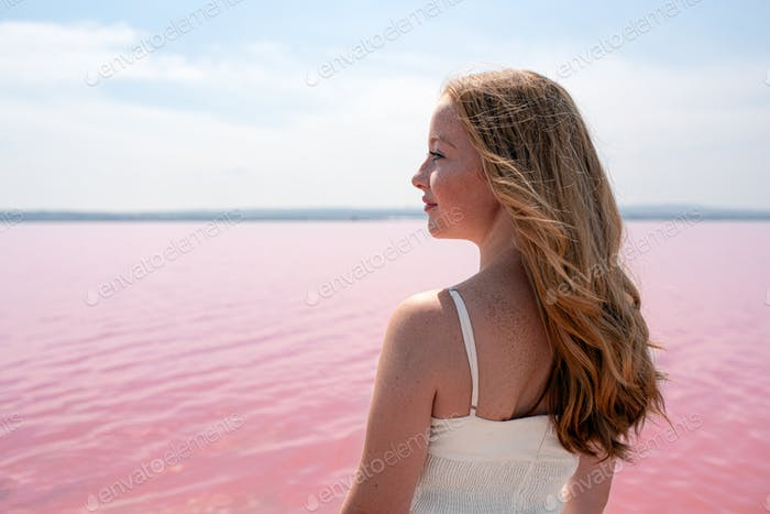 Side view of cute teenager woman wearing summer clothes standing on an amazing pink lake